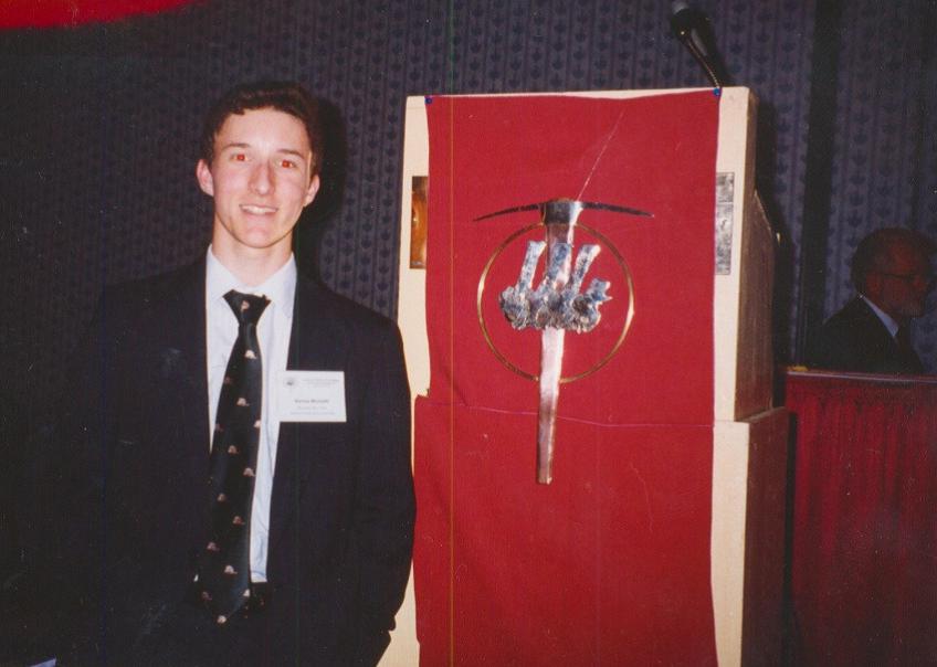 Barnas Monteith standing next to Society for Vertebrate Paleontology Logo